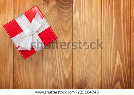 Red gift box over wooden background with copy space - stock photo