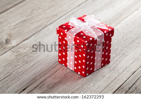 red gift box with  bow on wood background - stock photo
