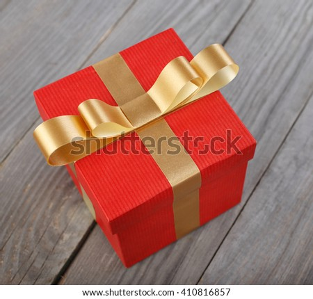 Red gift box with gold ribbon on the wooden table, top view - stock photo