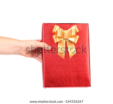 Red gift box with golden bow in hand. White background. - stock photo
