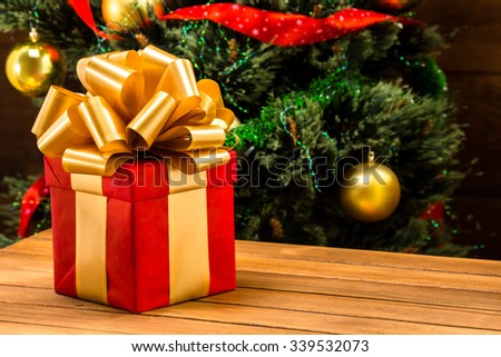 Red gift box with golden ribbon and bow represenred on wooden table. Beautiful Christmas present from Santa Clause in front of New Year tree. - stock photo