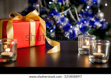 Red gift box with golden ribbon and candles in glass candlesticks on dark surface.  Christmas tree with decorations and lights in Home interior on the background. - stock photo