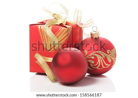 Red gift box with golden ribbons and xmas baubles on white background - stock photo