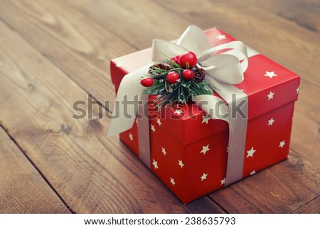 Red gift box with white ribbon and christmas decor on wooden background - stock photo