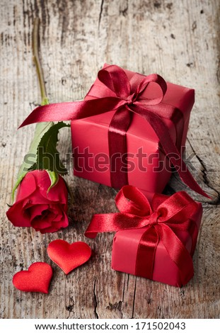 Red gift boxes and rose on wooden background - stock photo
