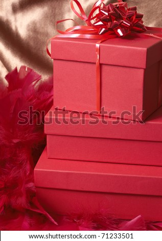 Red gift boxes with feathers and a bow on golden silk background - stock photo