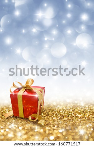 red gift on golden glitter  - stock photo