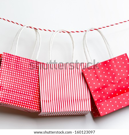 Red gift package paper bags hanging on a ribbon - stock photo