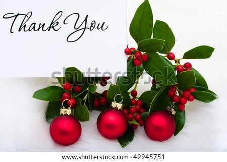 Red glass balls with a thank you card and holly and berries on a white fur background, Christmas balls - stock photo