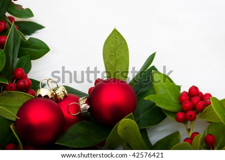 Red glass balls with holly and berries on a white fur background, Christmas balls - stock photo