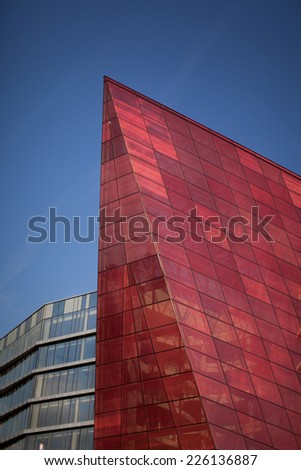 red glass building skyrocketing and showing new perspectives and greatness - stock photo