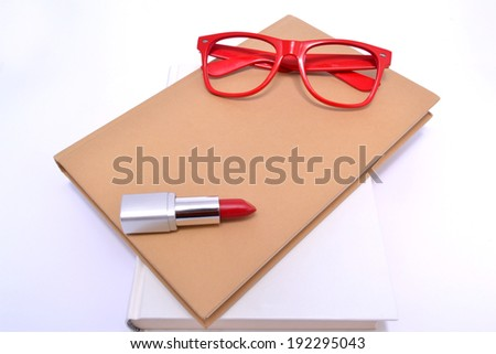 Red glasses, lipstick and books - stock photo
