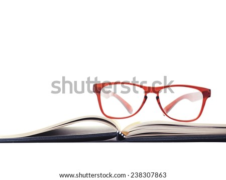 red glasses on a book over white background - stock photo