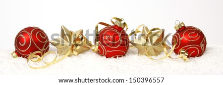 Red-golden baubles and golden stars on the snow - stock photo