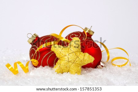Red-golden baubles and yellow star on the snow - stock photo