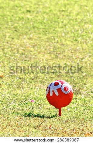 Red golf ball on tee over a blurred green. Shallow depth of field. Focus on the ball. - stock photo