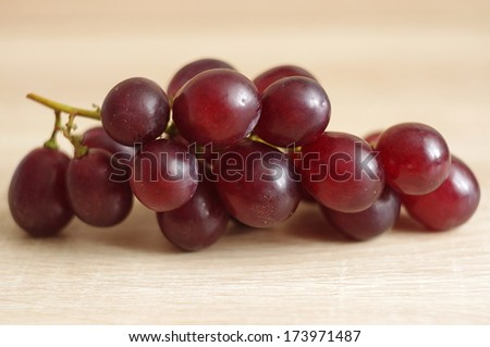 Red grape on wooden background - stock photo