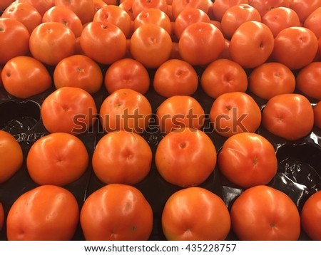 Red grape tomatoes in Row. Fresh Ripe Cherry Tomatoes. background of fresh tomatoes for sale at a market - stock photo