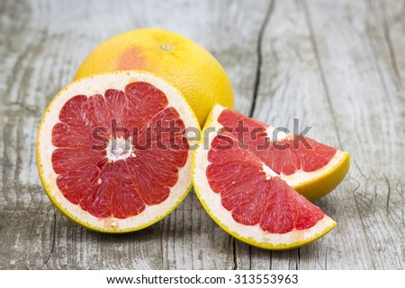 red grapefruit on old wooden background - stock photo