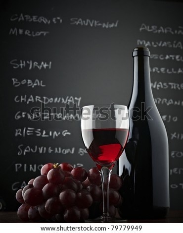 Red grapes, a bottle, a glass of wine and blackboard. Low-angle shot - stock photo
