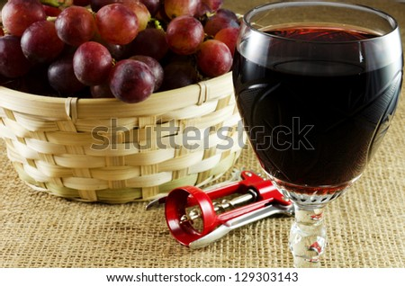 Red grapes in a basket wiht a glass of red wine and corkscrew on a jute texture - stock photo