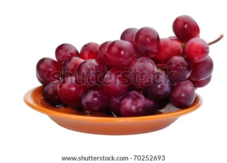 Red grapes on a brown dish. Isolated on white. - stock photo