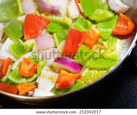 Red & green bell pepper, Spanish onion, minced garlic frying in olive oil.  - stock photo