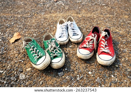 Red , green , blue Sneakers shoes walking on gravel road , Canvas shoes walking on gravel road , two sneakers behind each others as a sign of love , Sneakers shoes Couple  - stock photo