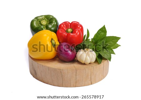 red green yellow capsicum onion garlic and basil leaves on wooden chopping board isolated on white - stock photo