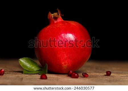 Red grenadine on the table with small seeds and a green leaf - stock photo