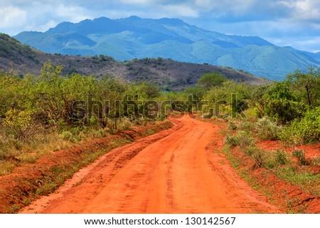 Red ground road and savanna landscape in Africa. Tsavo West, Kenya. - stock photo