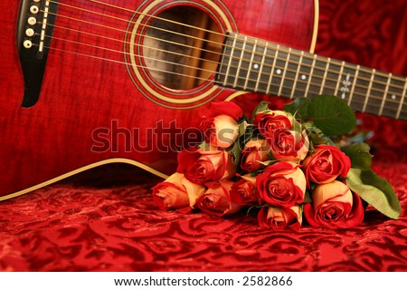 Red guitar and red roses on red velvet background - stock photo