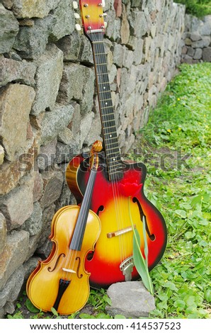 Red guitar and violin. - stock photo