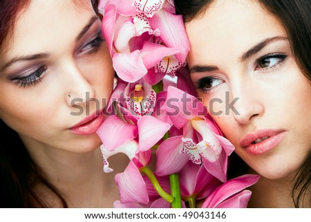 red hair  and brunette  woman beauty  portrait with orchid, studio shot - stock photo