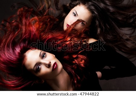 red hair and brunette woman with hair in motion, studio shot - stock photo