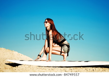 red hair beautiful woman with sunglasses on surfboard in sand, summer day - stock photo