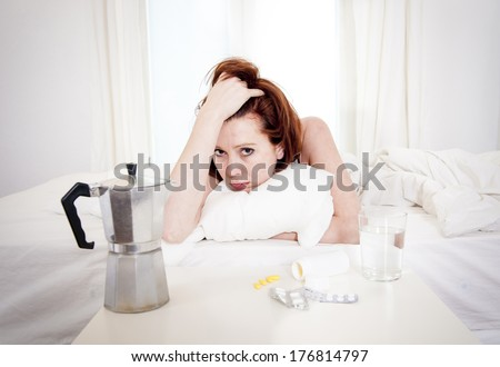 red hair girl hungover wanting coffee and medication to help with her hungover in bed - stock photo