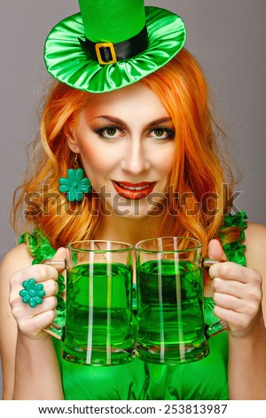 Red hair girl in Saint Patrick's Day leprechaun party hat having fun, holding a mug of ale - stock photo