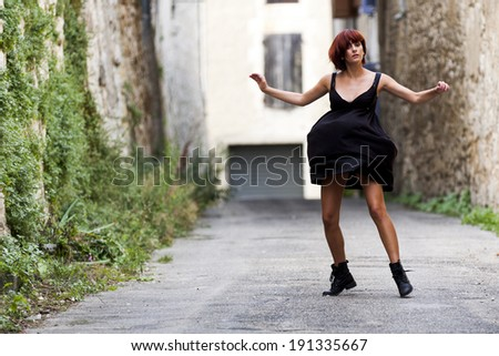 Red hair woman dancing alone in a street of a french village. She wears a black dress and clodhoppers. - stock photo