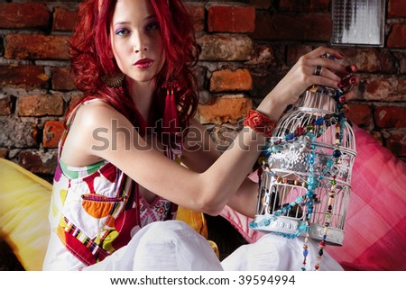 red hair woman holding a bird cage, indoor shot - stock photo