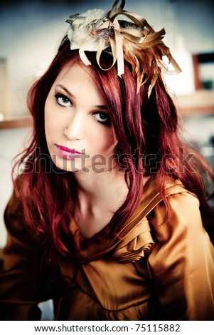 red hair woman in golden dress and headband with golden decoration indoor shot - stock photo