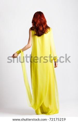 red hair woman in long elegant stylish yellow dress, full body shot, back view, studio shot - stock photo
