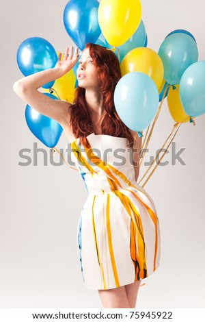 red hair woman in short elegant silk dress with a lot of yellow and blue balloons around her, studio shot - stock photo