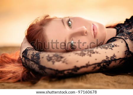 red hair woman lie on sand beach at sunset, portrait, small amount of grain added - stock photo
