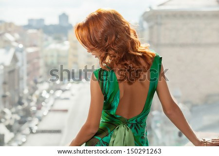Red hair woman. Rear view of beautiful young red hair woman looking away - stock photo