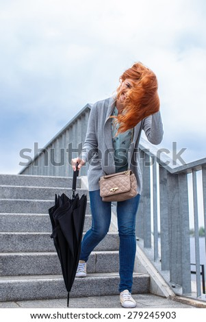 Red hair woman with ubbrella and casual clothes walking on street ladder - stock photo