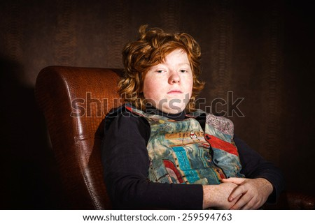 Red-haired expressive teenage boy sitting in arm-chair, studio portrait - stock photo