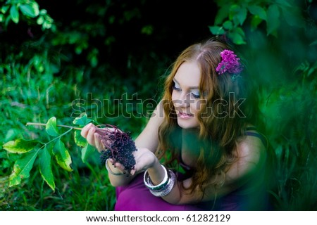 red-haired girl collecting berries in wood - stock photo