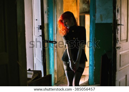 red-haired girl in handcuffs,many doors, many choices girl reading a book in an abandoned building, woman in black clothes, creative photography, mixed light, trouble,  with pale skin, fetish model - stock photo