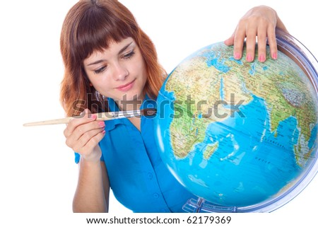 Red-haired girl is painting globe. Isolated on white background - stock photo
